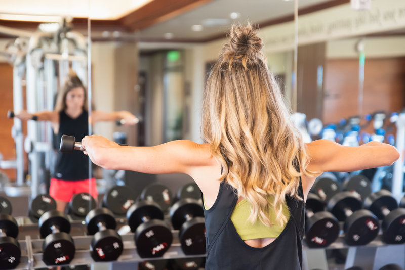 woman working out lifting weights at gym