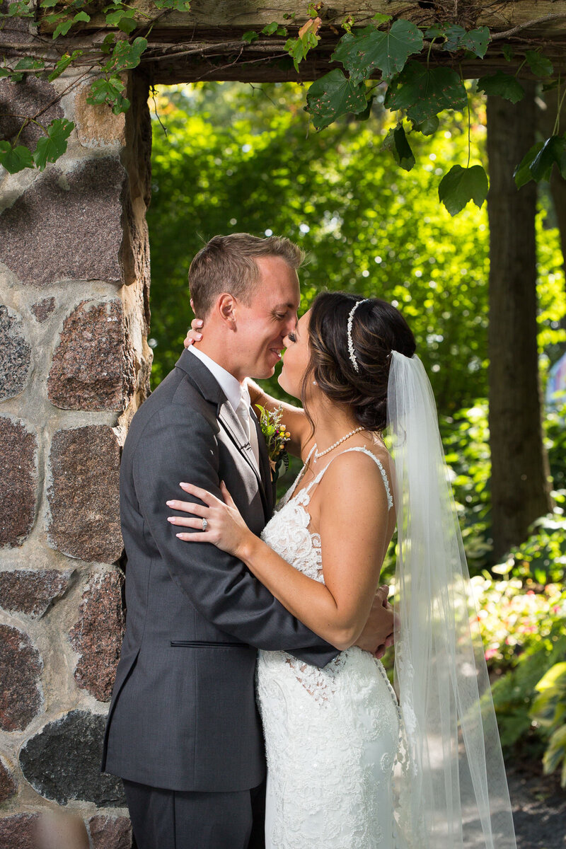 bride and groom kissing at the green bay botanical gardens
