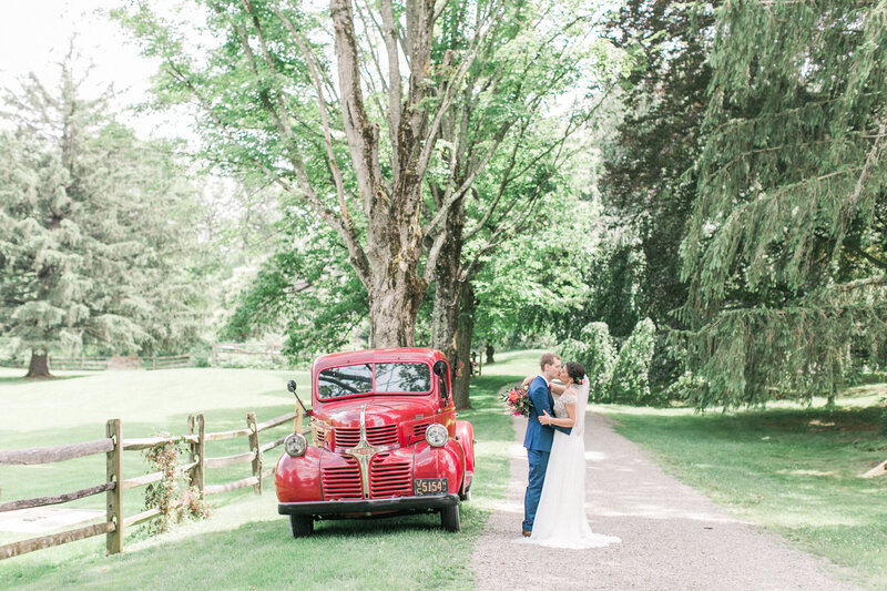 Bride and groom kiss and embrace on tree lined path next to vintage red pick up truck