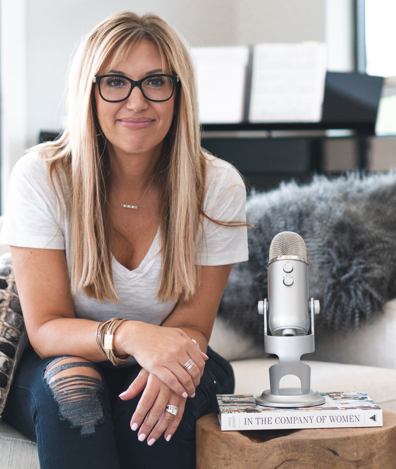 Woman wearing black glasses sitting down next to microphone