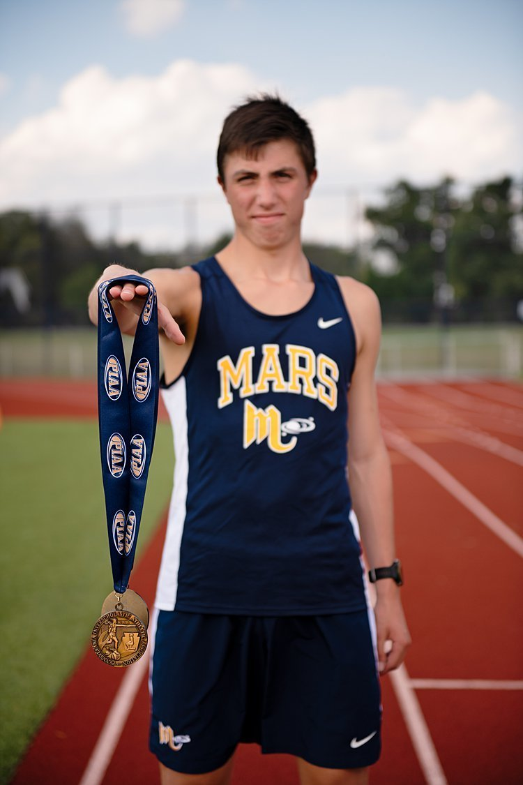 High school senior boy in track uniform holding gold medal at Mars High School stadium in Pittsburgh, PA