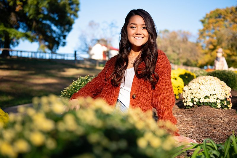 High school senior girl in rust-colored cardigan seated among Fall Mums at Round Hill Park in Elizabeth, PA