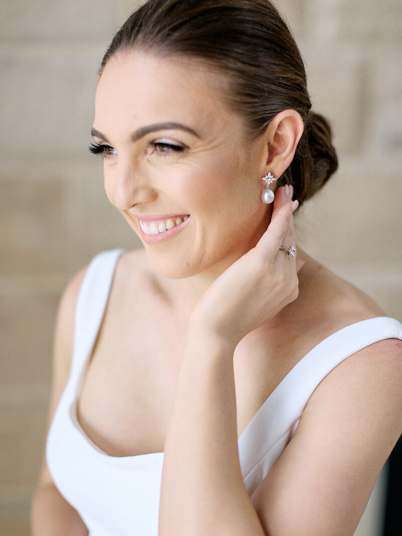Bride adjusting her earings while getting ready