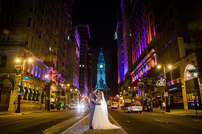 Bride and groom standing on Broad street in front of the Philadelphia City hall at night with colorful uplighting