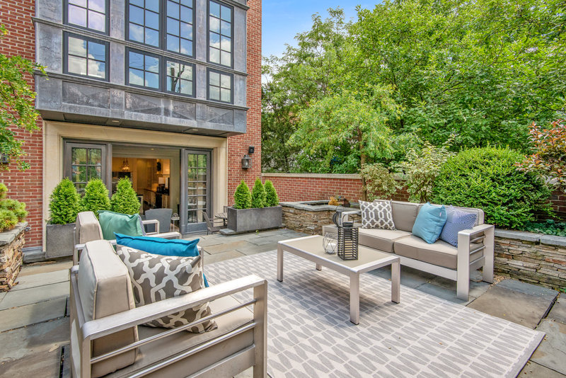 Vibrant Outdoor Patio with beige chrome loveseats and coffee table and outdoor accessories surrounded by plants and trees