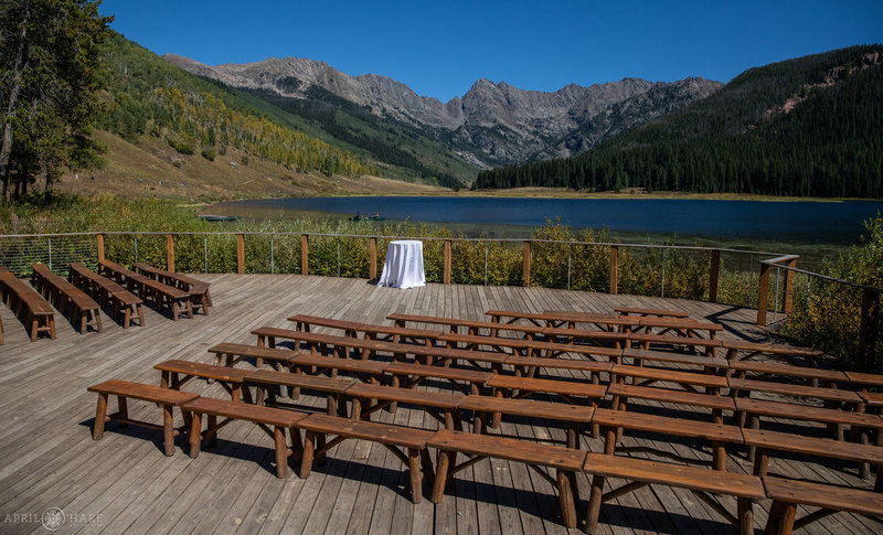 View of the ceremony space on the outdoor deck with wood benches at Piney River Ranch