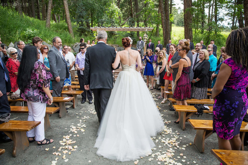 Father and bride walk down the aisle on the Evergreen Terrace at The Pines at Genesee in Colorado