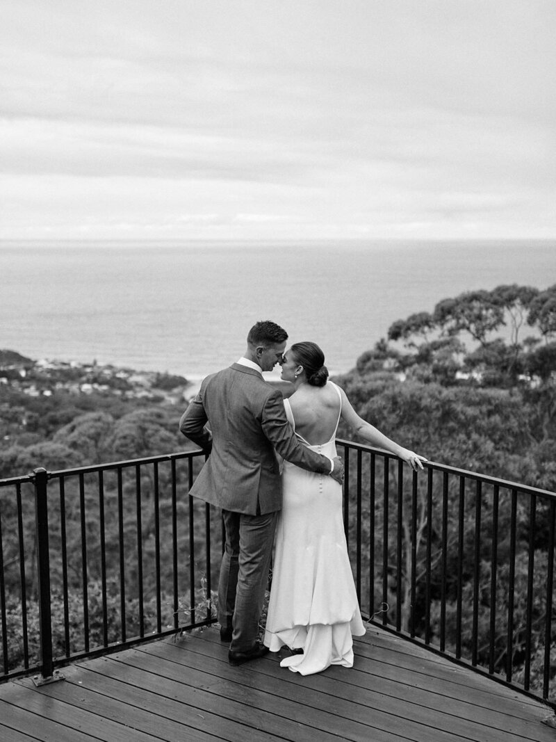 Bride and groom leaning on balustrade with view over ocean