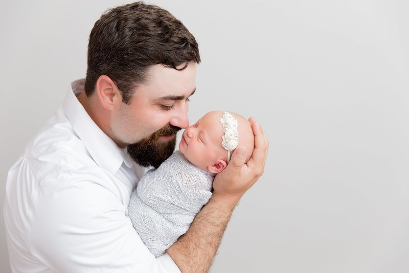 dad with newborn baby girl in greys and white
