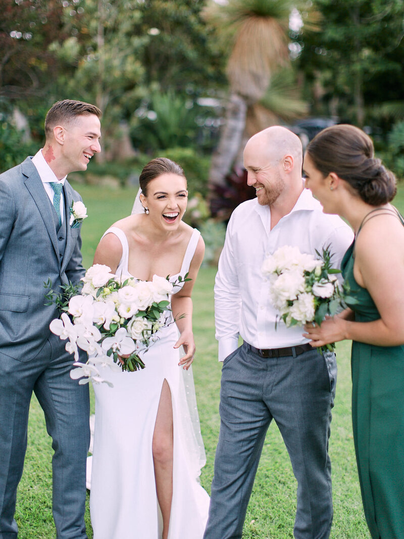 Bridal party laughing on lawn
