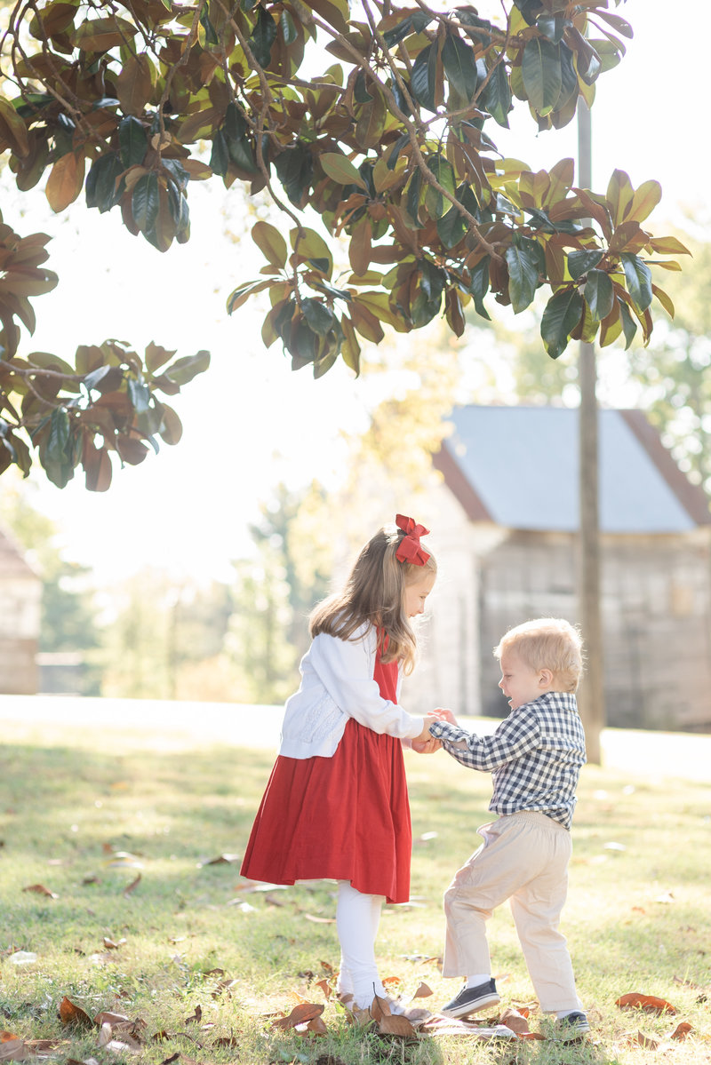 An older sister wearing a red dress is playing ring a round the rosie with her younger brother in a park in Nashville
