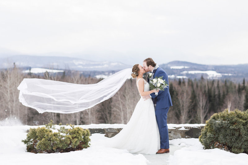 groom kissing wife with veil in wind on top of snowy mountain