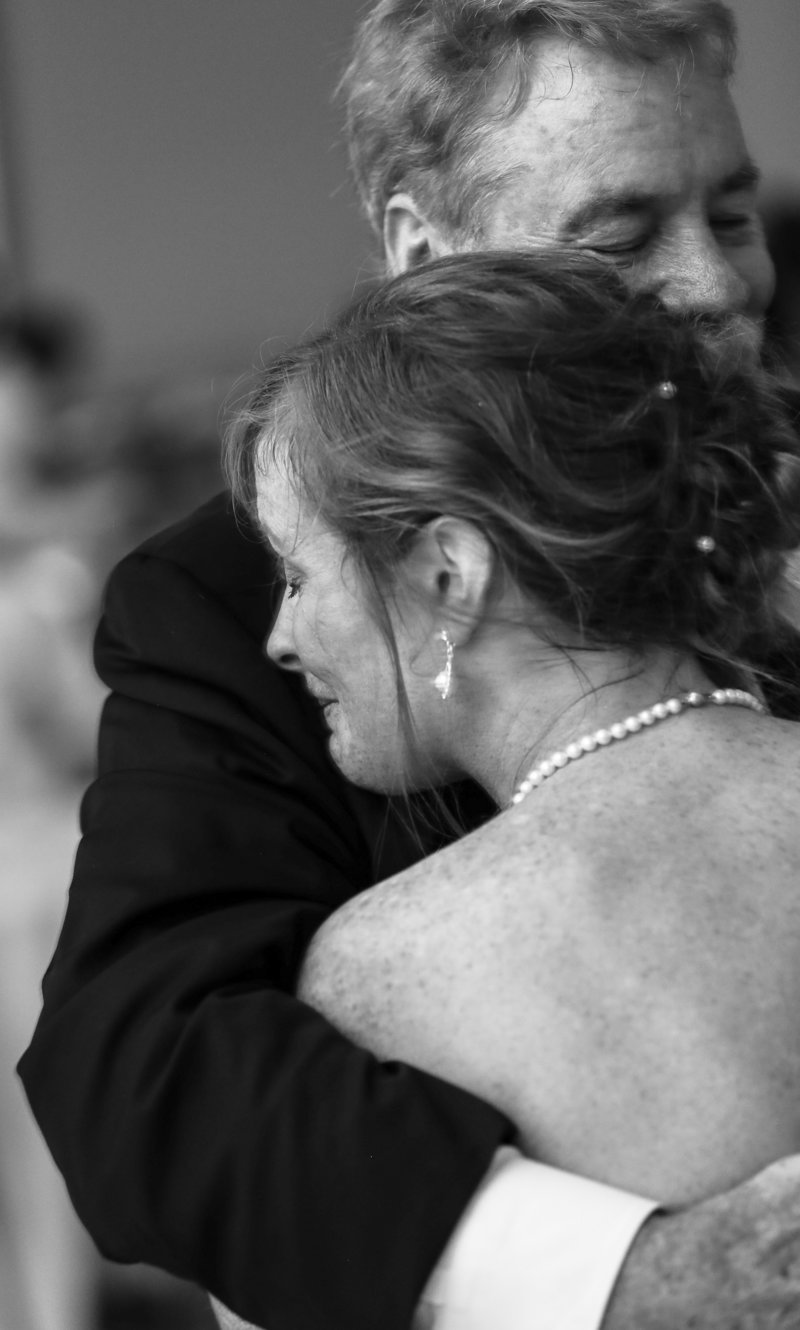 Bride cries on her father's shoulder during father daughter dance at Masonic Temple wedding reception in Erie, PA