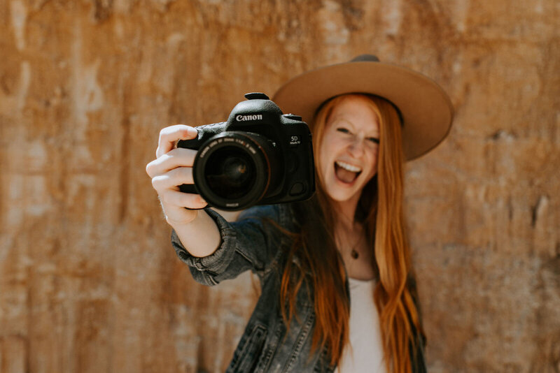woman wearing a hat and smiling while holding camera