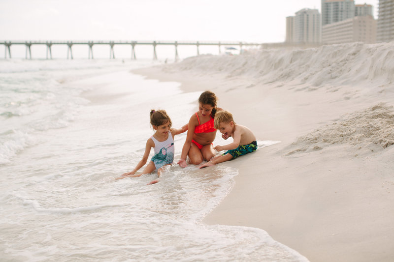 three children playing on a beach during a vacation