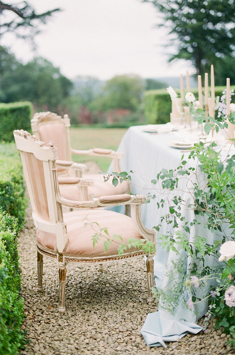 Antique neutral dining chairs and a blue cloth table with billowing greenery for a garden wedding rehearsal dinner