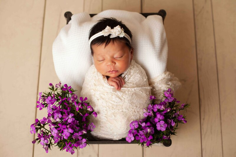 dark haired newborn girl in a  prop with purple b flowers and white wrap