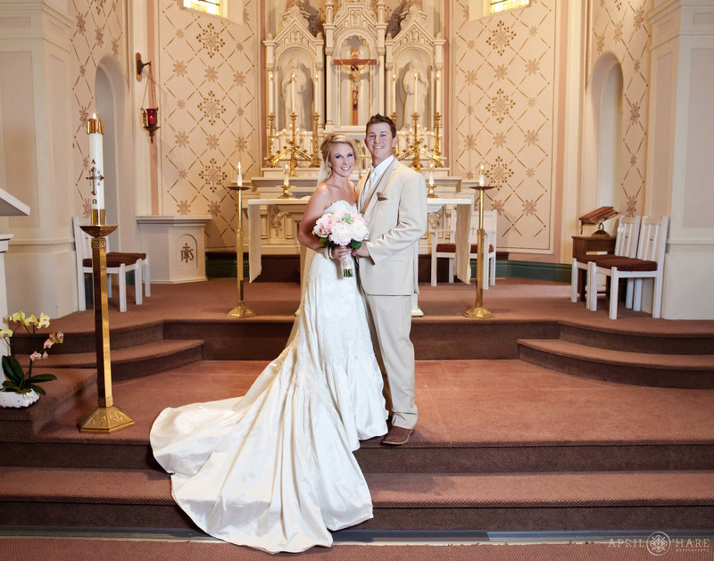 Couple stands on the altar area for their wedding portraits at Sacred Heart of Mary in Boulder