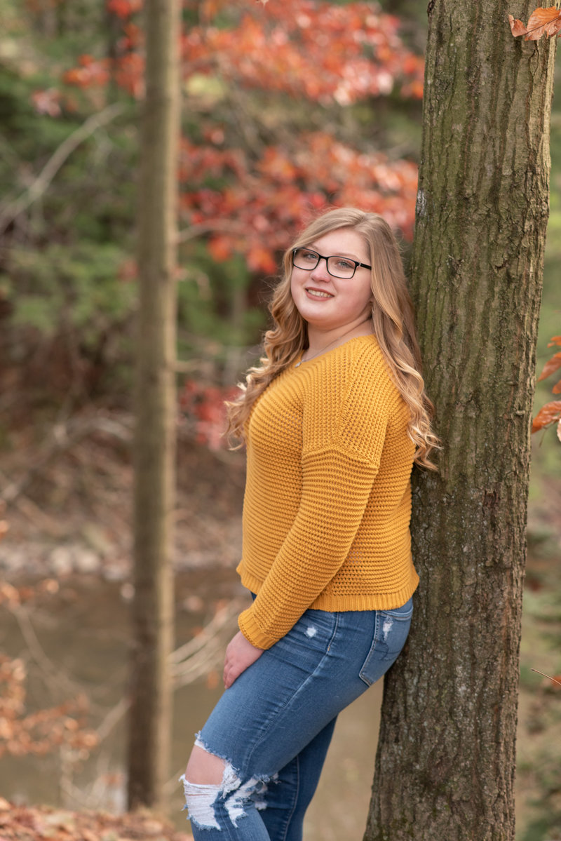 Senior Girl in gold sweater leaning against tree