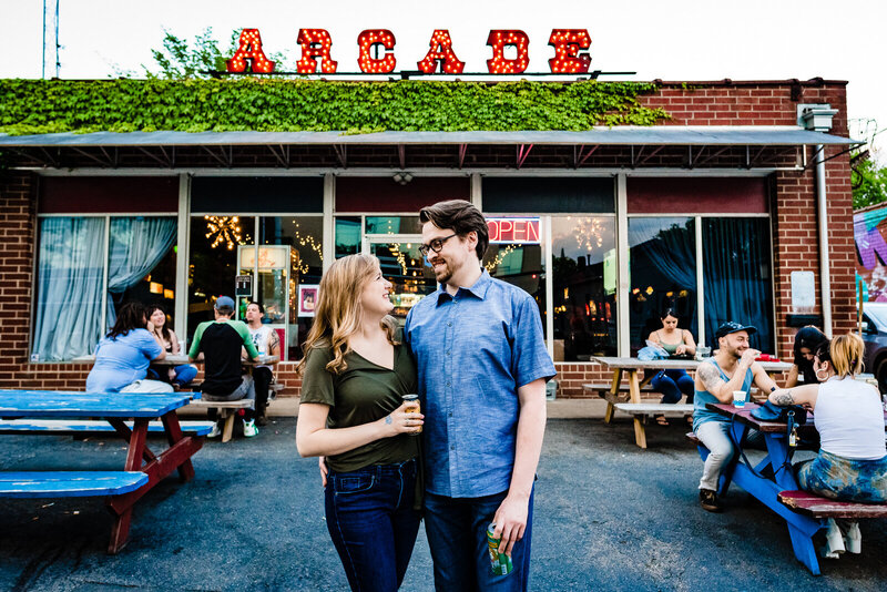 Engaged couple poses in front of a the Arcade sign at the baxter barcade in Carrboro, NC