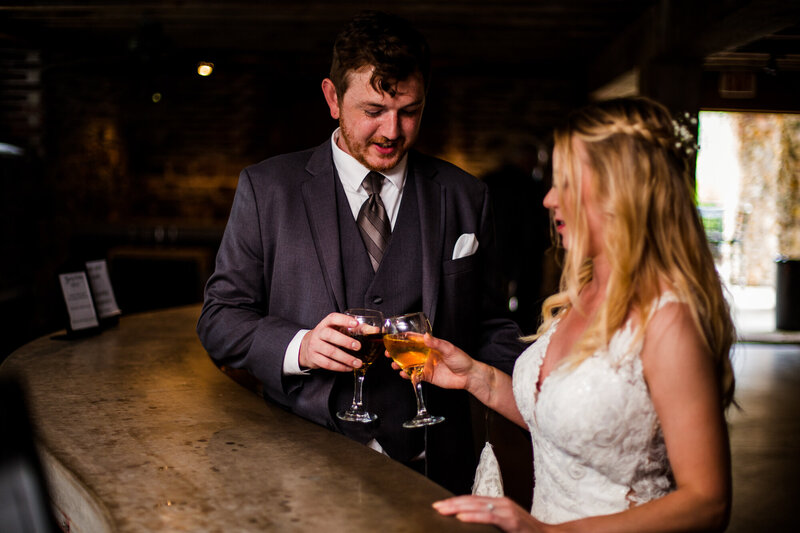 Bride and groom share a toast at the bar during their Quincy cellars wedding  reception