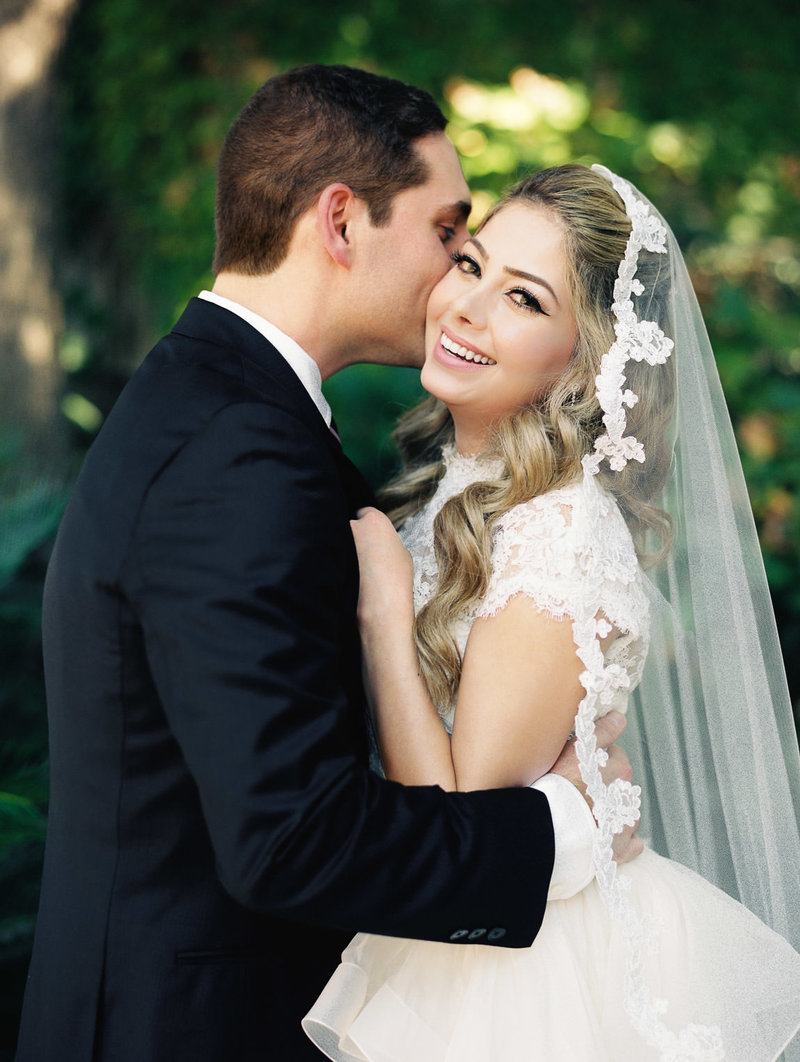 groom embracing bride in wedding dress and veil as she smiles in front of greebery