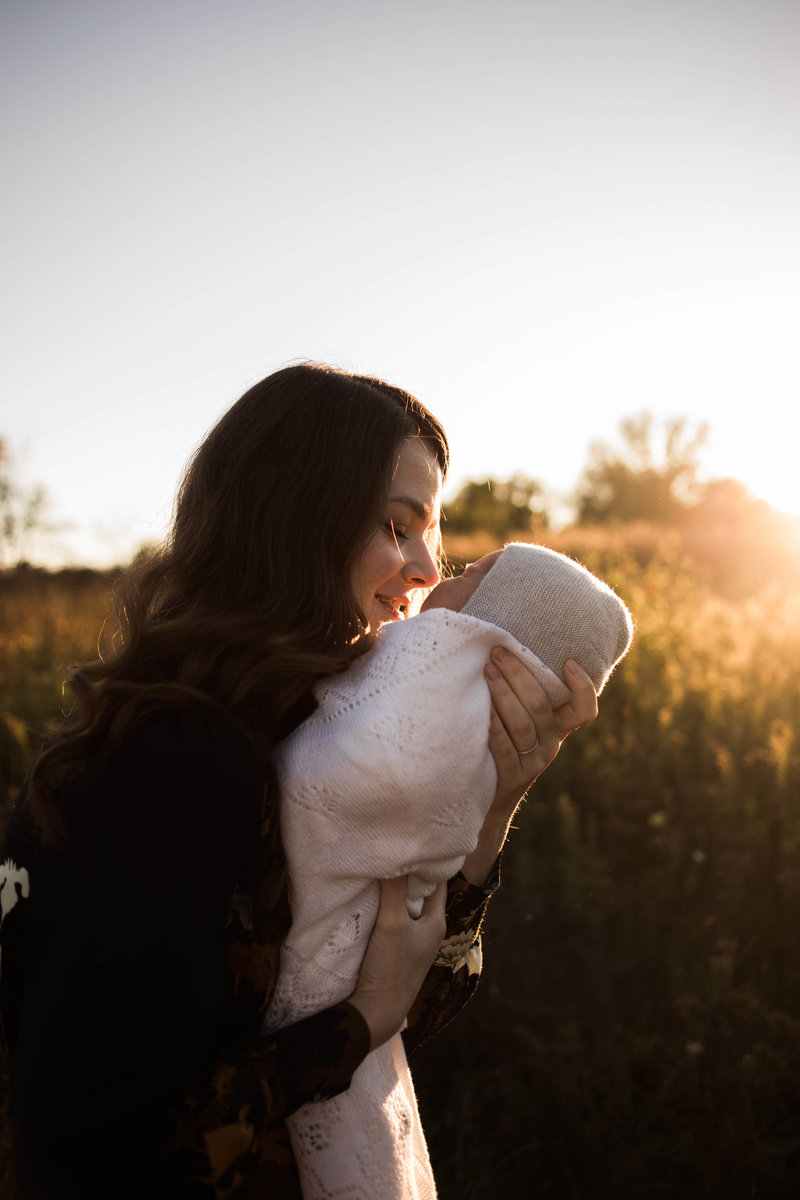 Mother holding her newborn baby outdoors at sunset, photo taken by Elle Baker Photography