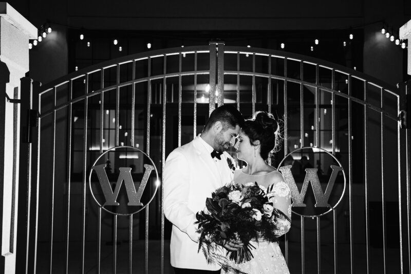 Married couple embracing in front of gates on wedding day