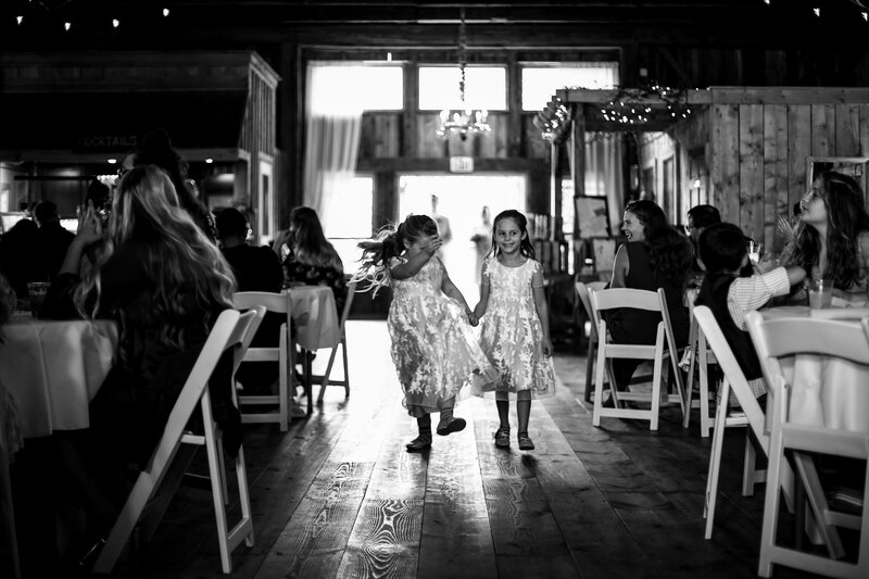 Little girls dance between tables at Port Farms wedding ceremony