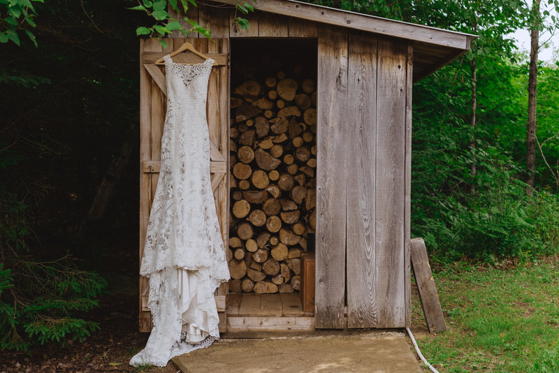 wedding dress hanging from wood shed
