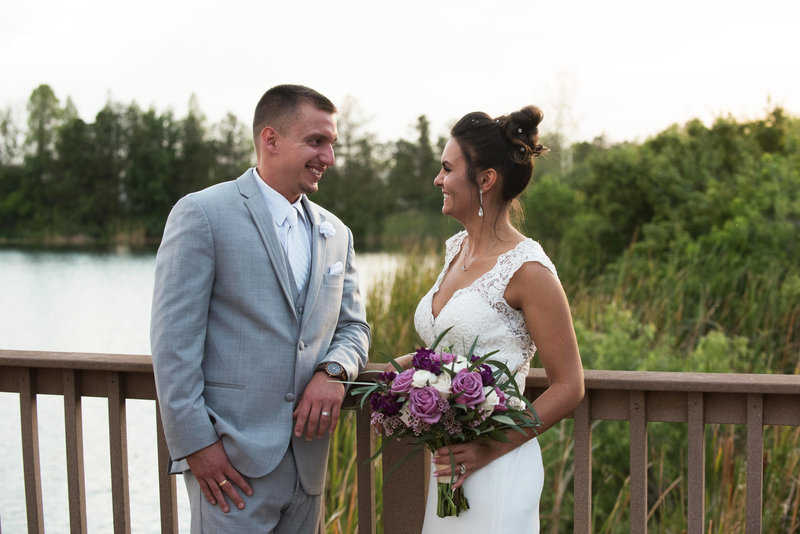 Bride and Groom leaning on a fence overlooking a lake talking