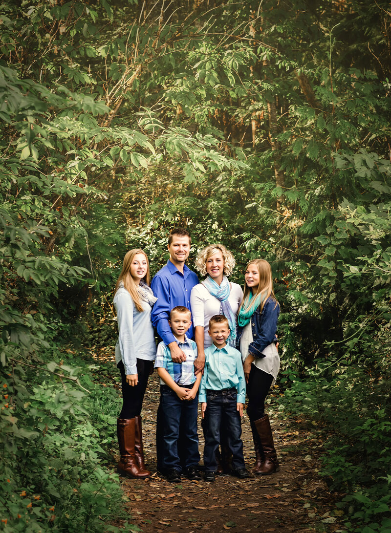 Family poses for portrait in a beautiful forest