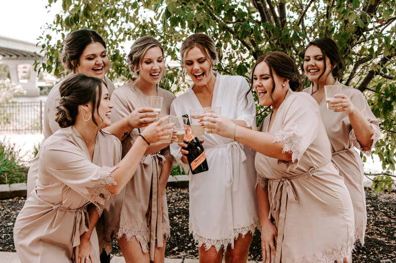 bride and bridesmaids wearing robes and drinking champagne