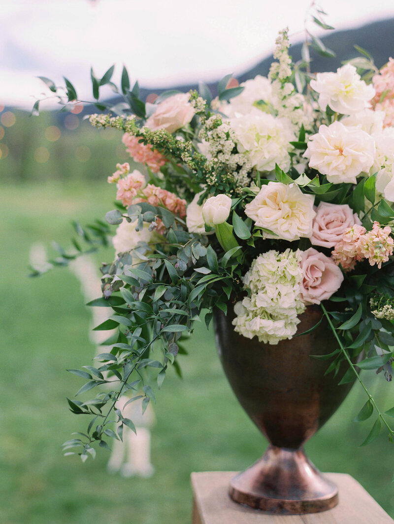 Testimonial photo, a large bouquet of pink roses, white flowers, and long green stems in a bronze vase