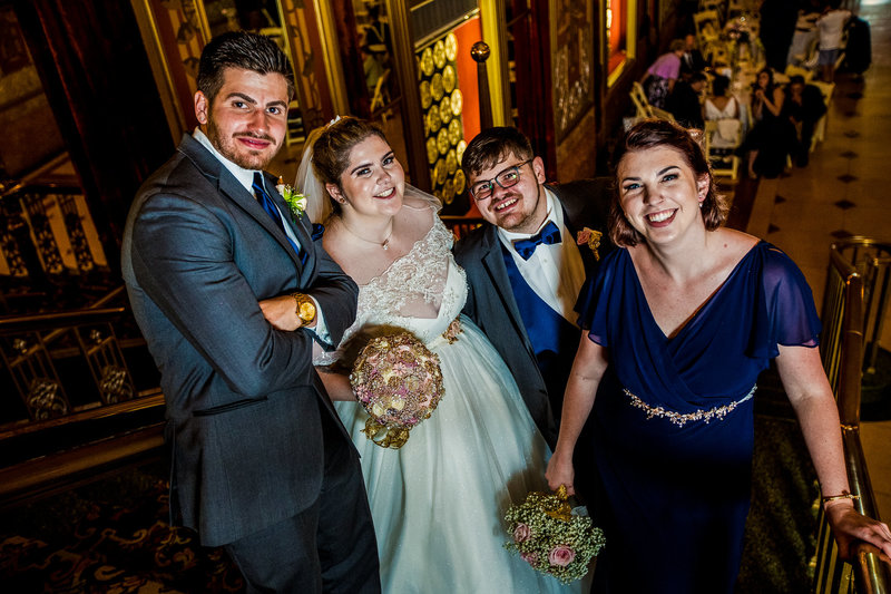 Bride and groom pose with best man and maid of honor during Warner Theatre wedding