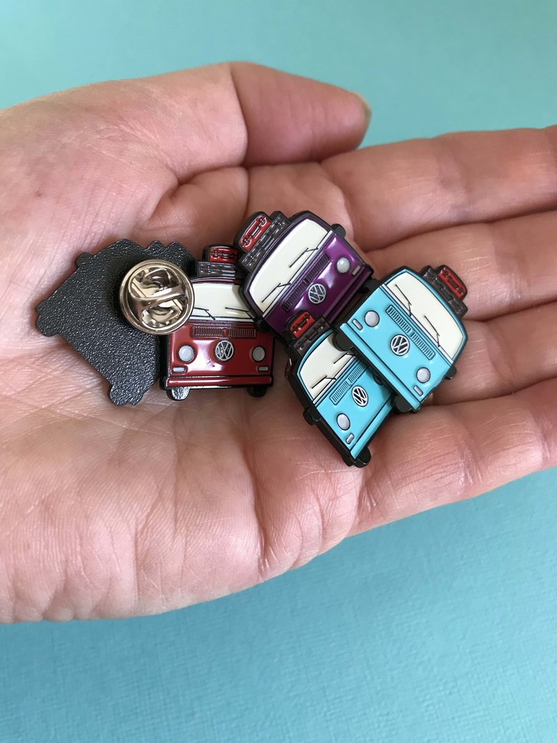 Lapel pins of nz kombi hire badges sitting in palm of hand to show size