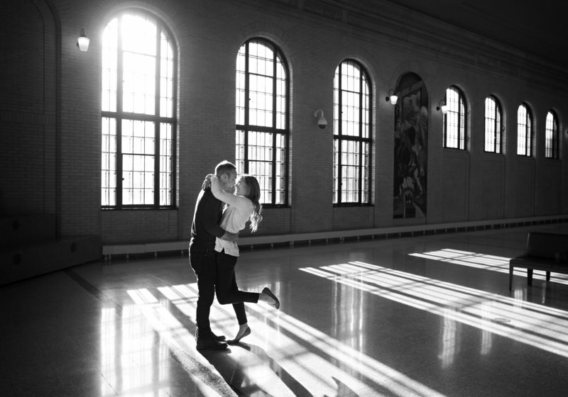 Engaged couple are embracing at Union Station in St. Paul, MN, in front of large historic windows.
