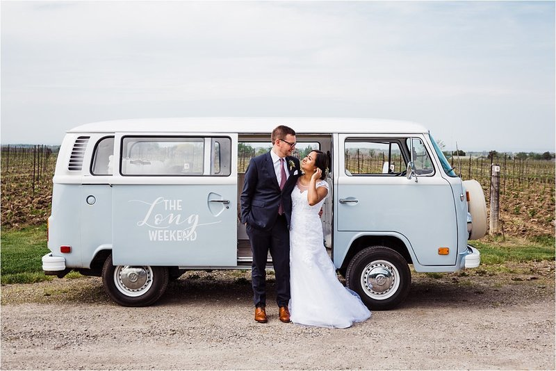 Bride and Groom look in each others eyes in front of their wedding Kombi at Cave Spring Vineyard Wedding Venue in Jordan Ontario