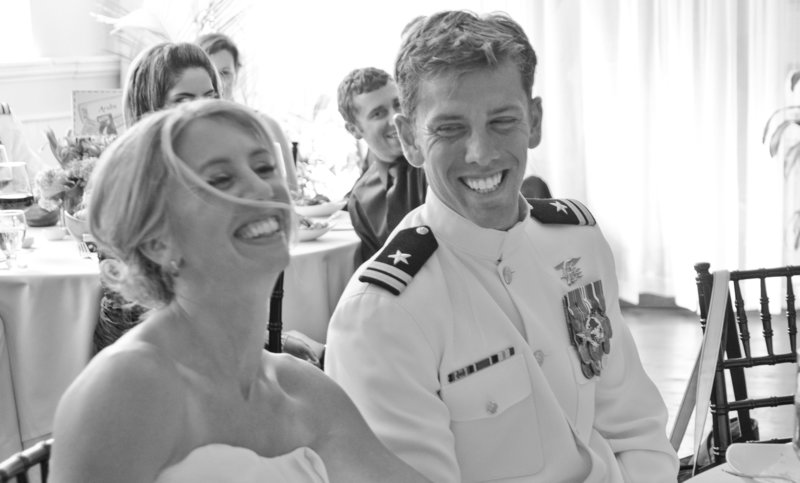 Bride & groom in navy uniform smile & laugh during wedding reception in Portland, Maine