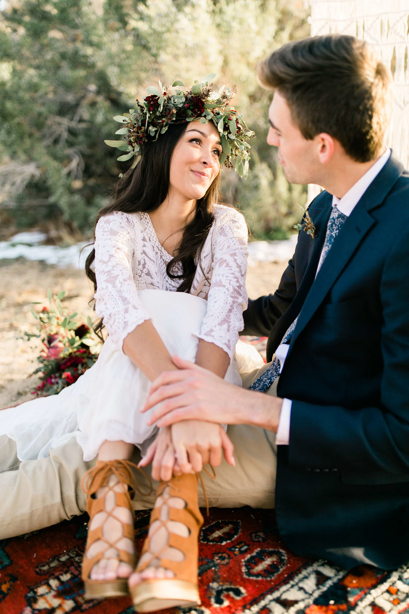 Bride looks up at her groom as they sit on a brightly patterned  boho rug.