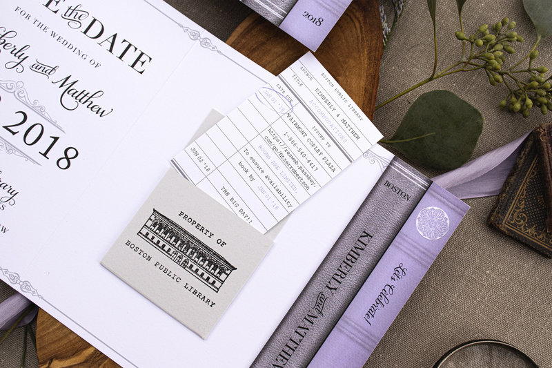 Folded library or book themed save the date featuring beautifully designed book ends and a library due date pocket stamped with a custom illustration of the Boston Public Library. Accommodations information placed on library due date card.