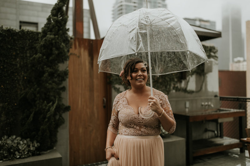 Bride in blush wedding dress and clear umbrella on her wedding day at the Natural History Museum in Los Angeles on New Years Eve