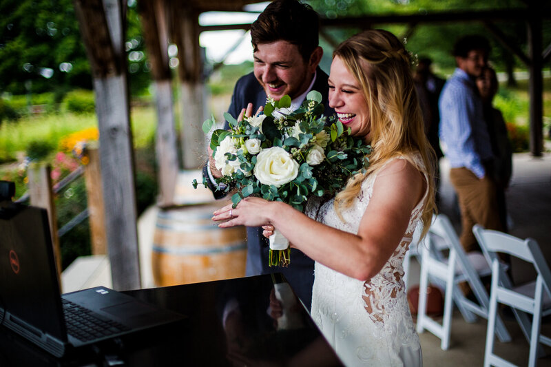 Bride and groom show off rings to their virtual guests at the end of their Quincy cellars wedding ceremony