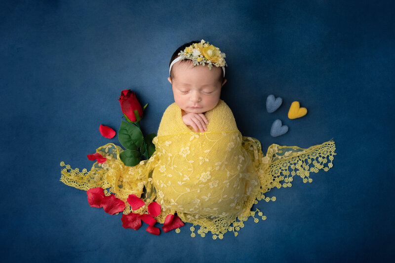 baby girl swaddled in yellow against a blue background with a red rose