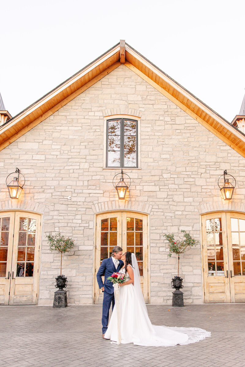 A bride and groom kiss in front of the Stone House of St. Charles.
