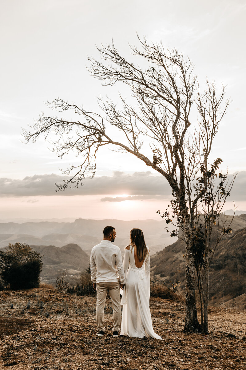a-couple-in-white-dress-standing-in-view-of-the-mountain-2917382