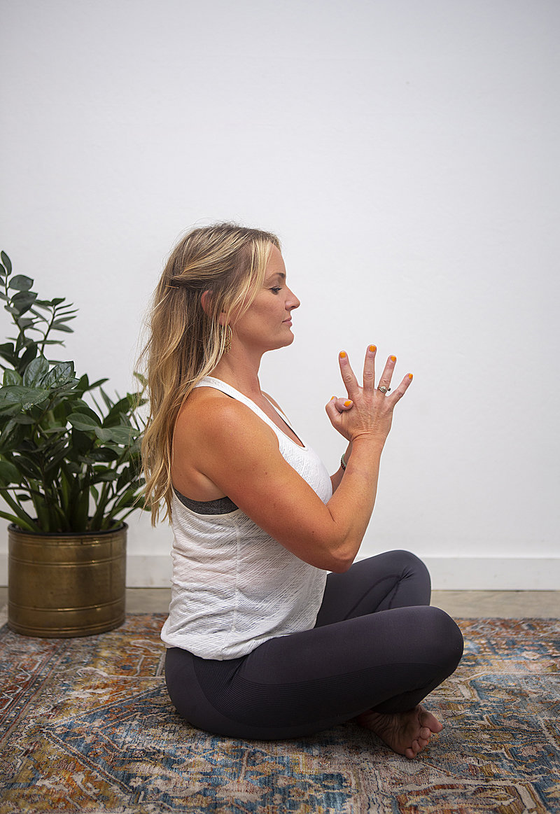 Profile view of female yoga student holding lotus prayer pose during yoga class at Hotsource Yoga in Aptos