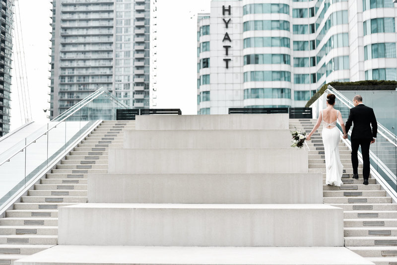 Couple walk up the stairs on the terrace of this Malaparte wedding