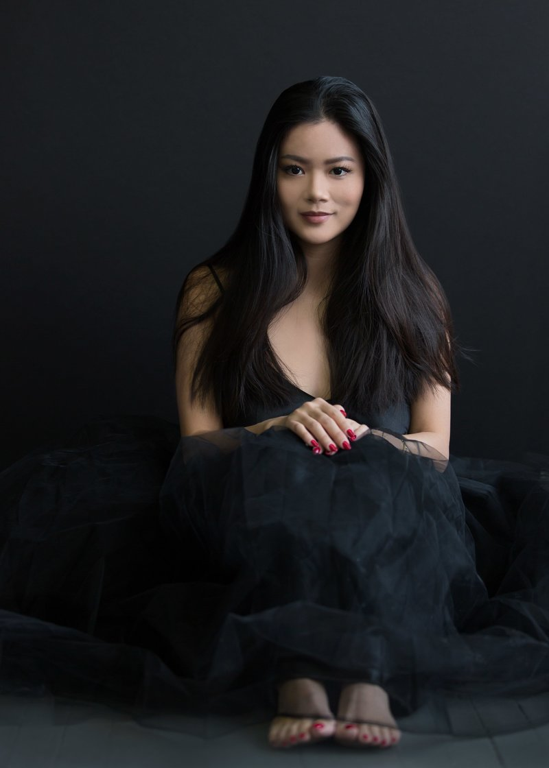 Portrait of a woman wearing a black tulle skirt on a black background