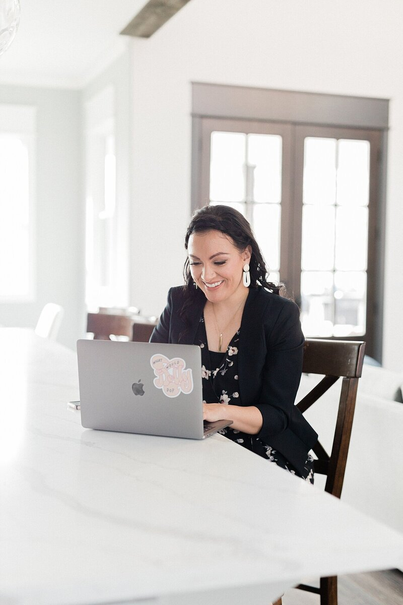 woman with black hair sitting at a kitchen island working on a macbook pro and smiling